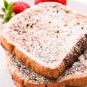 brioche french toast on a plate with powdered sugar and strawberries