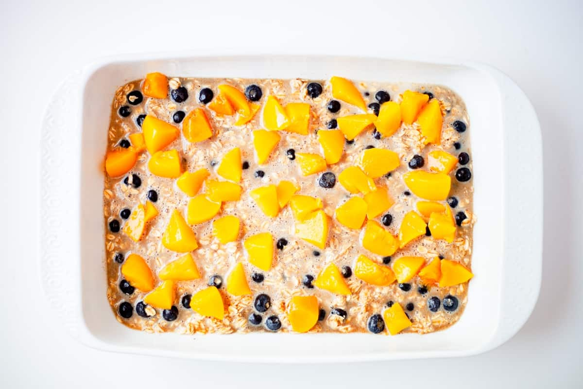 a full baking dish of peach berry baked oatmeal unbaked