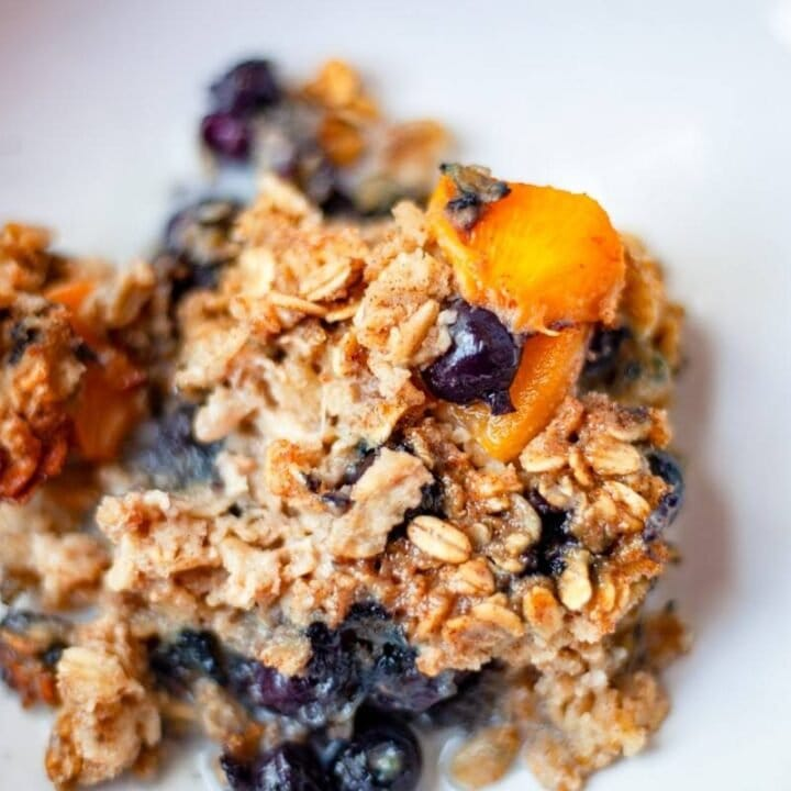 peach berry baked oatmeal in a bowl with almond milk close up