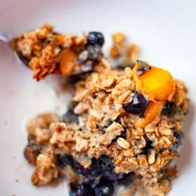 peach berry baked oatmeal in a bowl with almond milk
