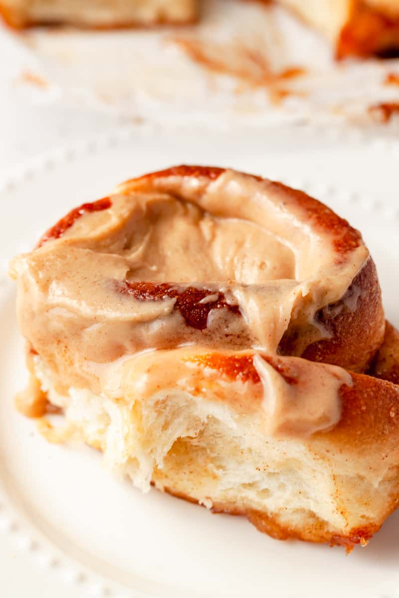 a single caramel apple pie cinnamon rolls with caramel icing on a plate close up