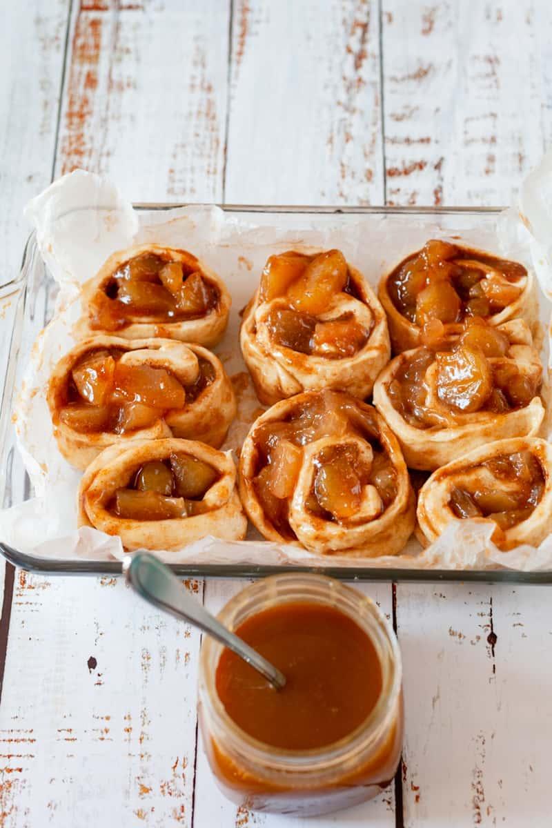 a jar of caramel sauce with sweet rolls
