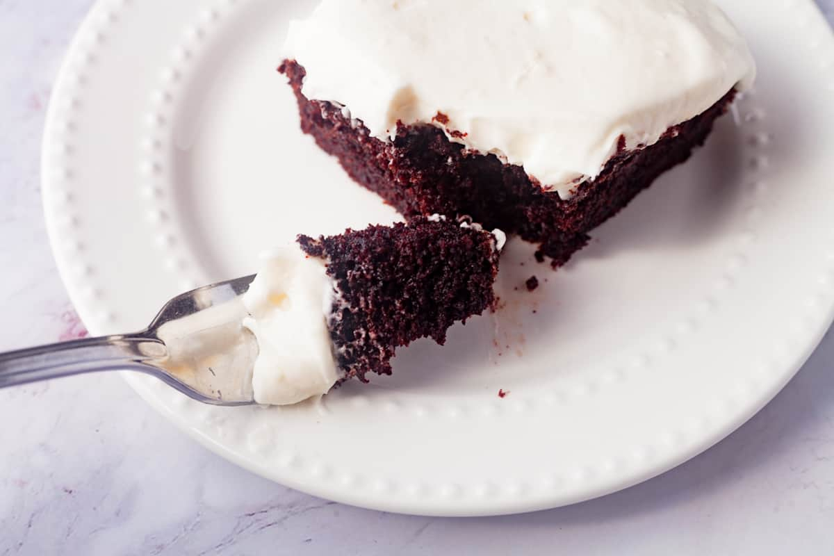 slice of chocolate sour cream cake on a white plate with a fork