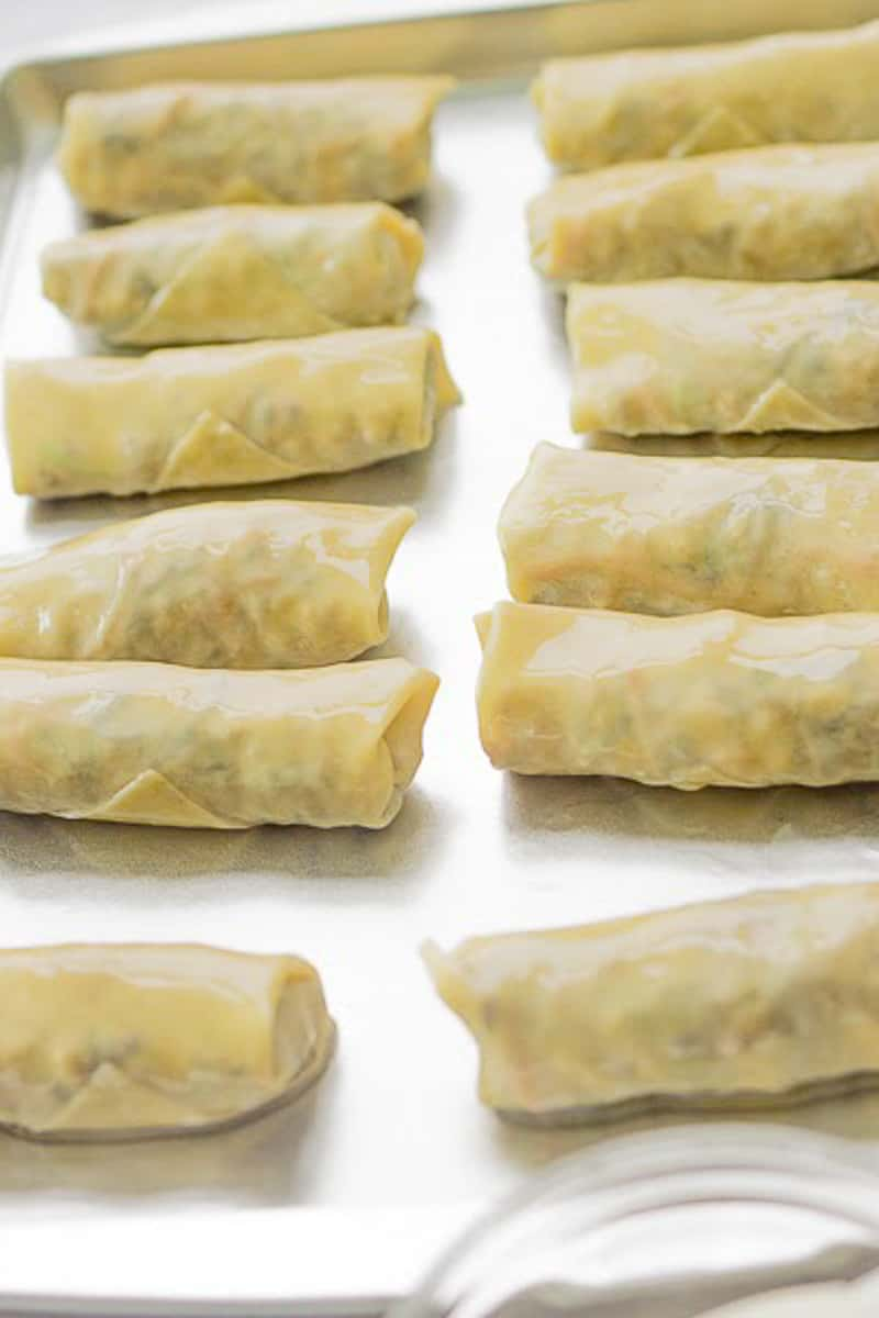 baking sheet lined with uncooked egg rolls
