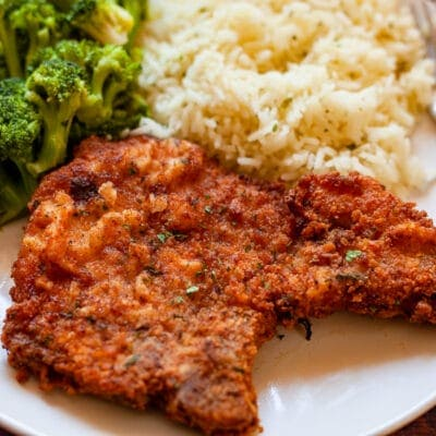 pork chop on a plate with rice and broccoli