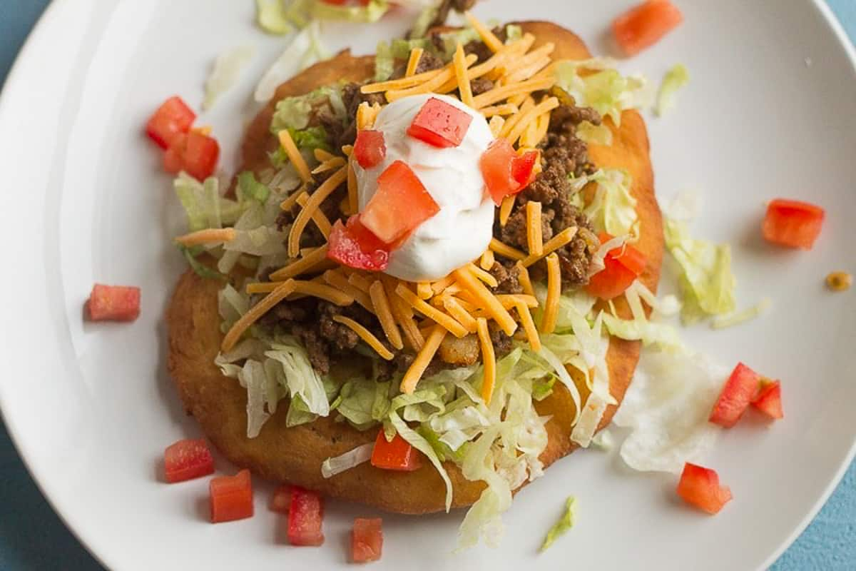 Frybread navajo taco topped with meat and cheeset