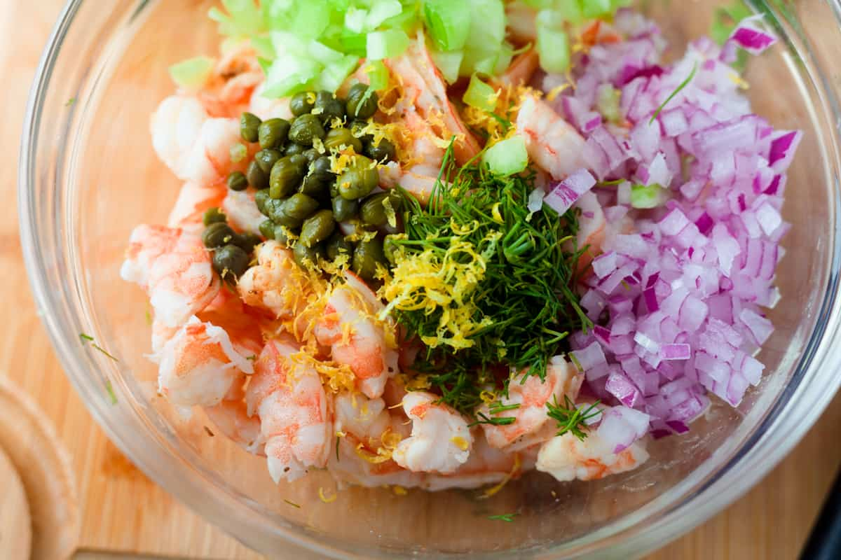 chopped shrimp with capers, dill, lemon zest, and red onion in a bowl