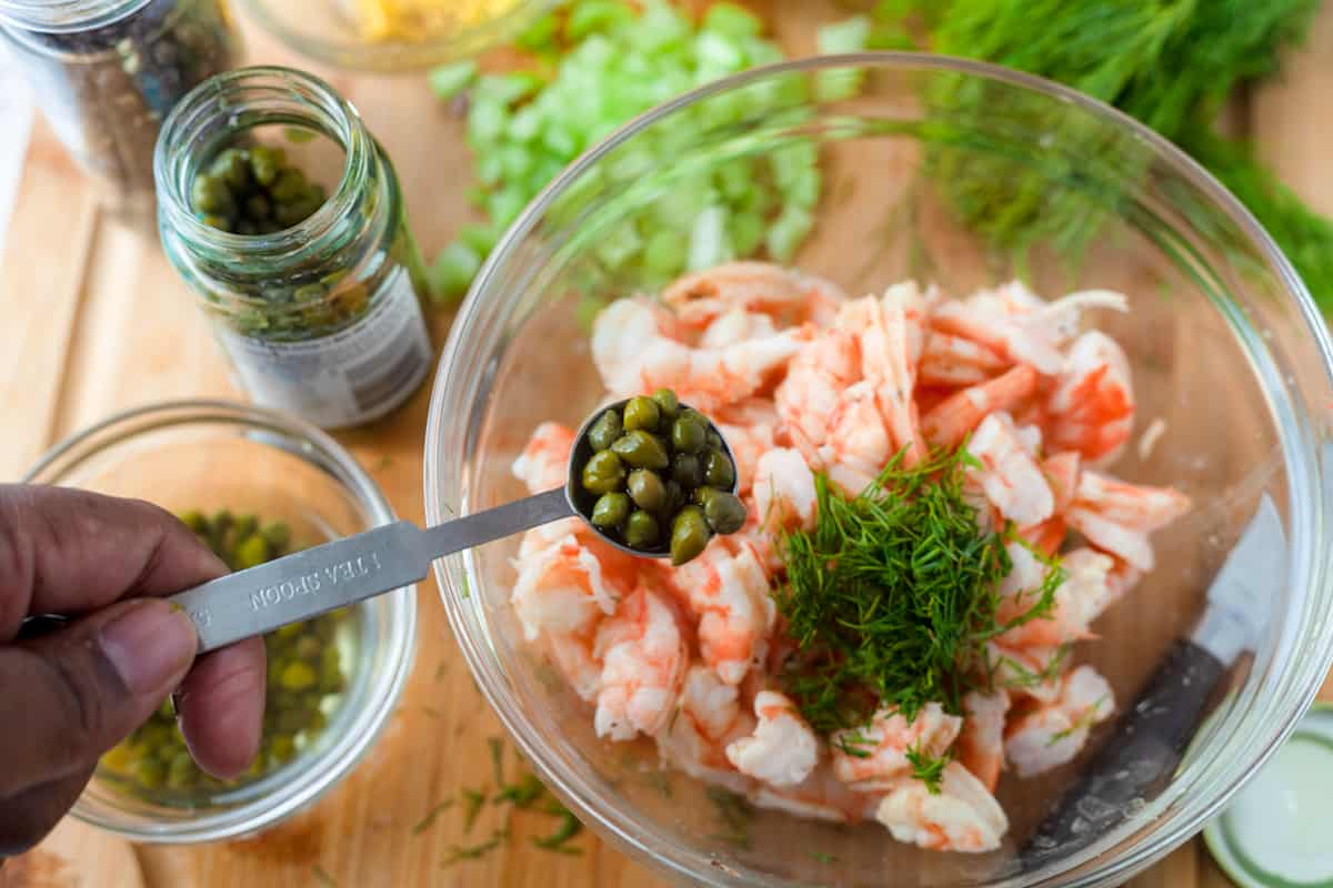 adding capers to a bowl with chopped shrimp