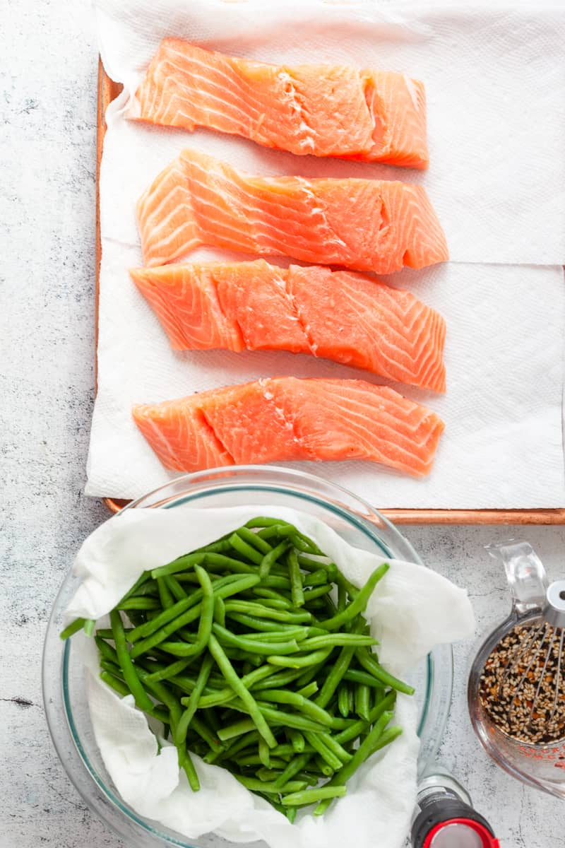 fresh salmon with a bowl of green beans