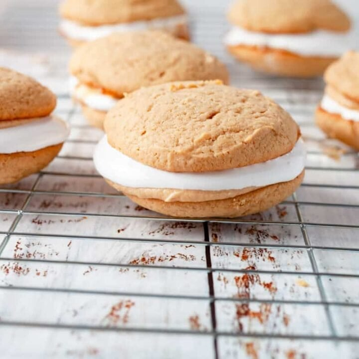 peanut butter and marshmallow whoopee pies on a wore rack