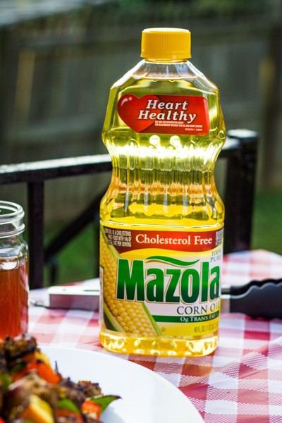 a bottle of mazola corn oil on a picnic table