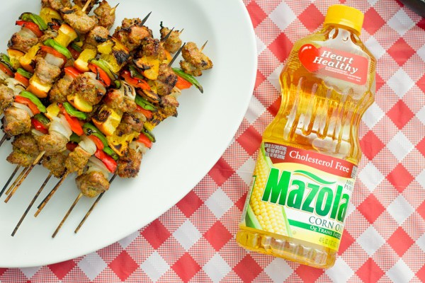 pork tenderloin kabobs on a platter with a bottle of mazola corn oil on a table