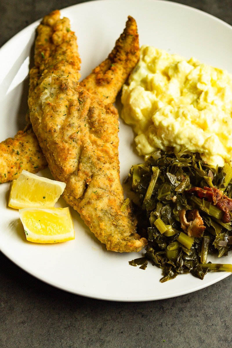 southern fried whiting fish on plate with greens and potato salad