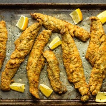 southern fried whiting fish on a tray with lemon wedges