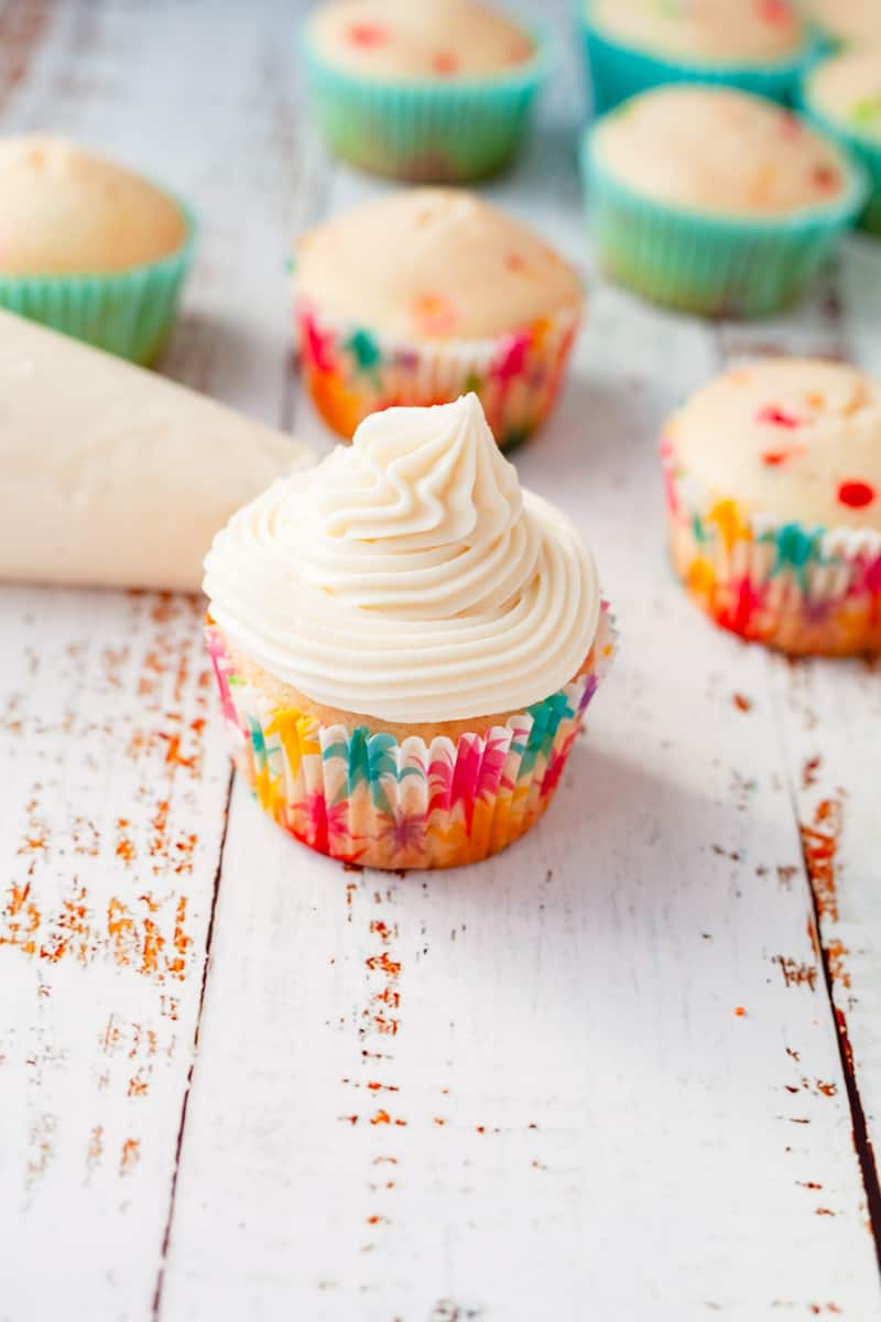almond buttercream frosting on a funfetti cupcake