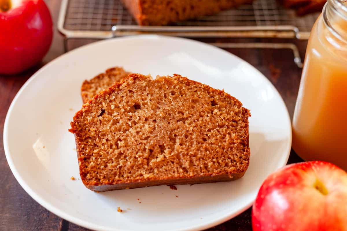 apple cider bread on a plate with an apple and a glass of apple cider close up
