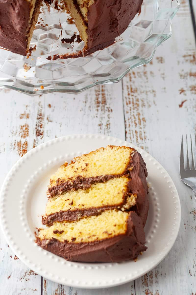 a slice of 3 layer cake with a whole cake on a stand
