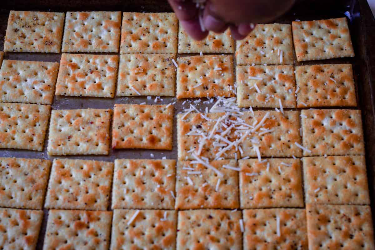 sprinkling cheese on crackers