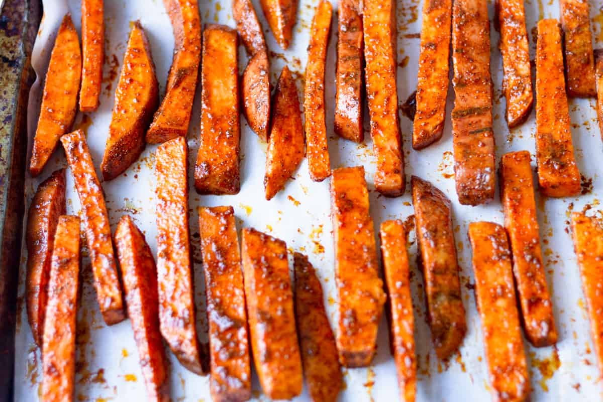 seasoned sweet potatoes on a baking sheet