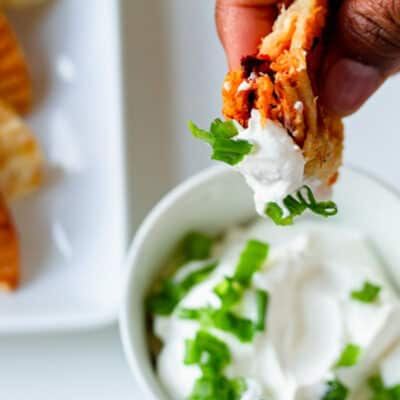 chipotle chicken empanada dipped in sour cream