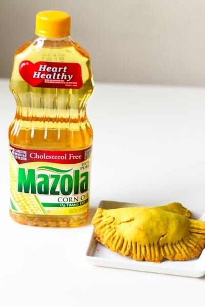 a bottle of Mazola® Corn Oil next to healthier Jamaican beef patties