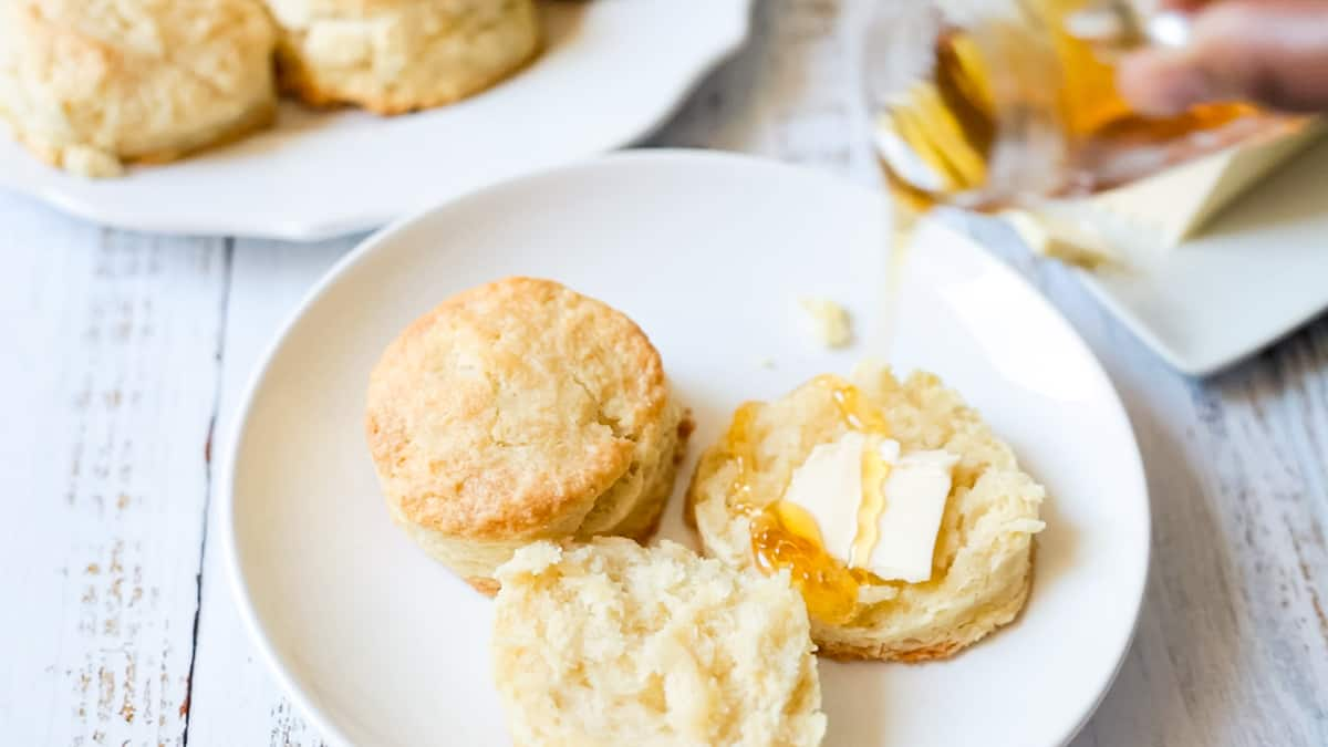 pouring honey on buttered biscuits