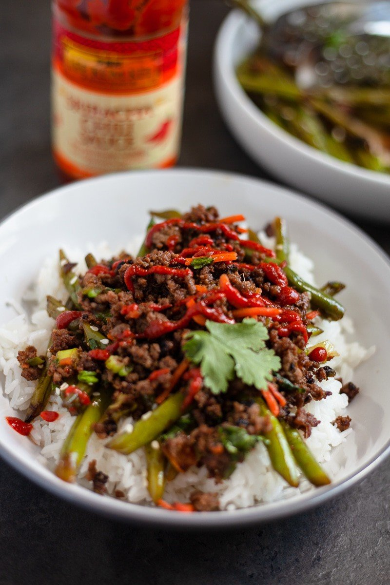 asian beef bowl over green beans and rice in a dish