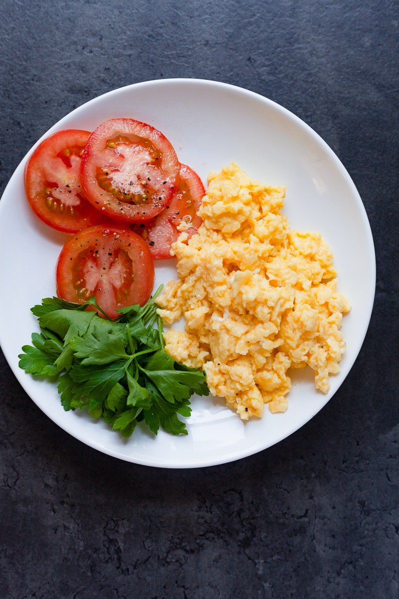cheesy scrambled eggs on a plate with tomato and parsley vertical