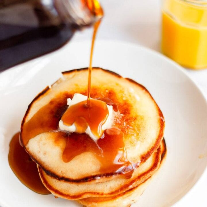 syrup poured over pancakes and butter close up