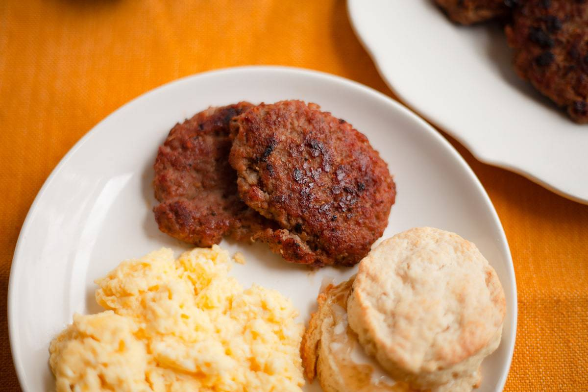sausage patties on a plate with scrambled eggs and a biscuit