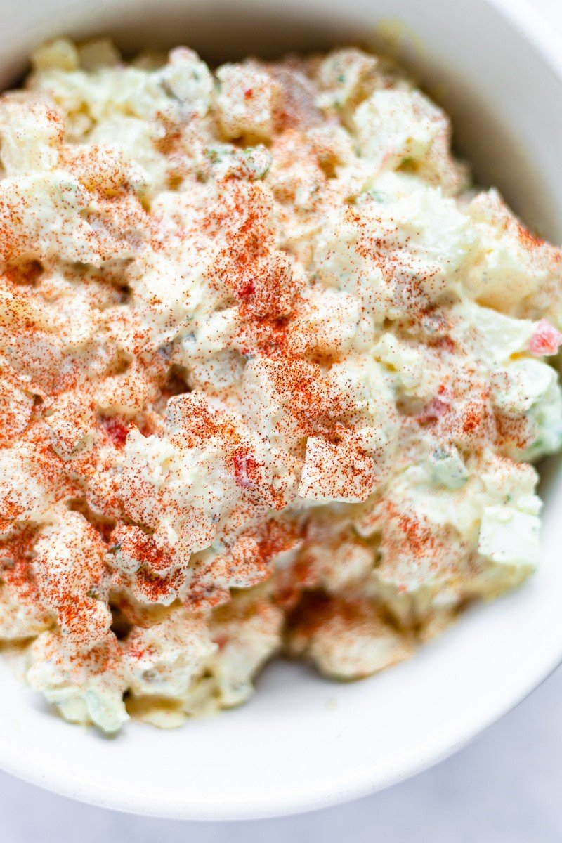 potato salad in a bowl sprinkled with paprika vertical