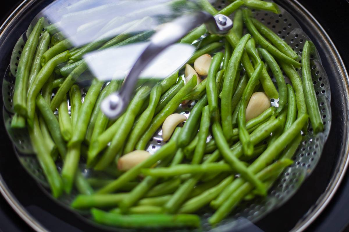 pot top over steaming green beans and garlic