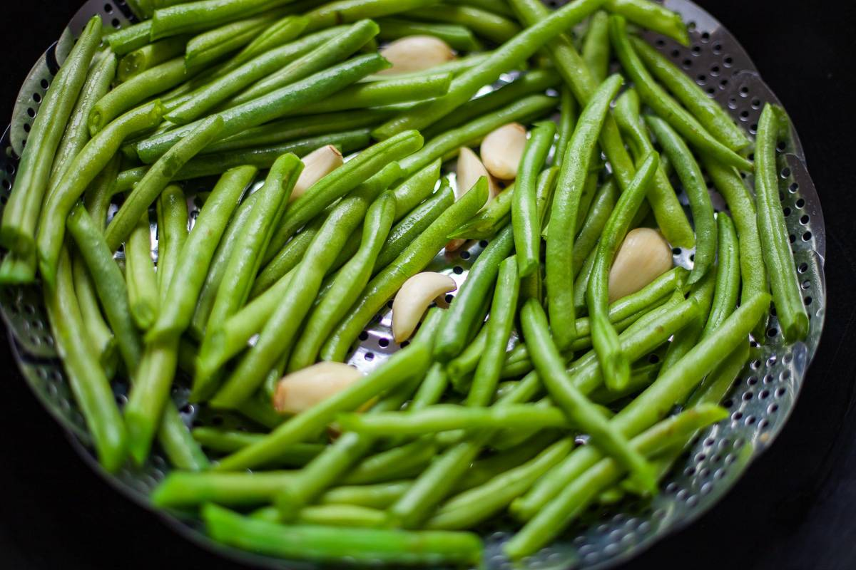 green beans and garlic in a steaming basket
