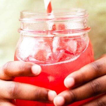 little brown hands holding a glass of watermelon liemade
