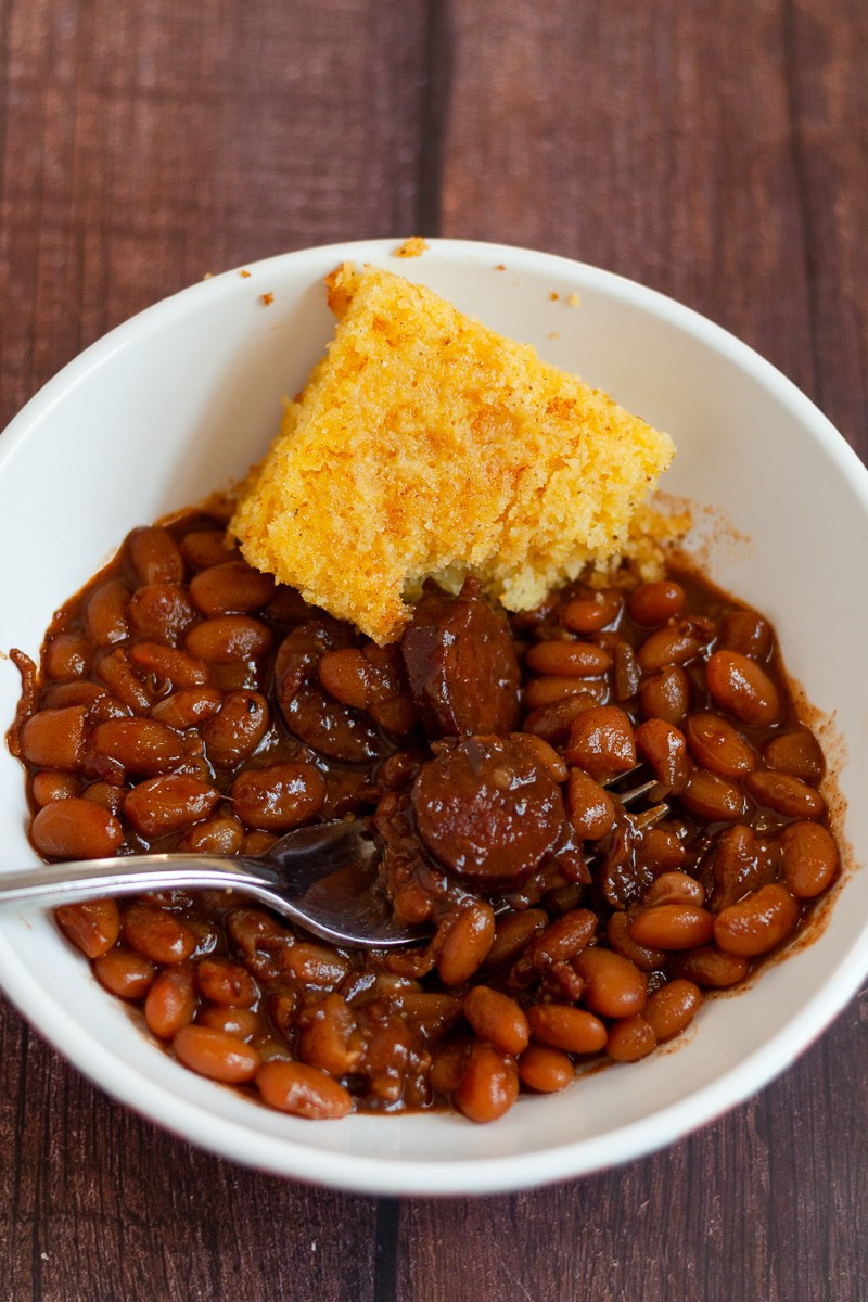 smoked sausage in a bowl with a slice of cornbread vertical