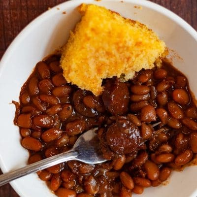 smoked sausage in a bowl with a slice of cornbread