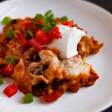 chicken lasagna topped with tomato and sour cream