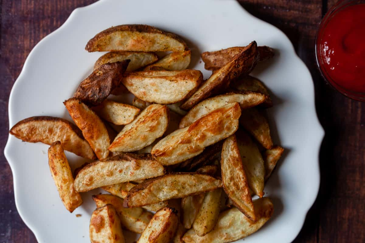 plat of seasoned potato wedges with a side of ketchup