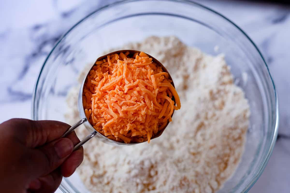 adding cheddar to a bowl