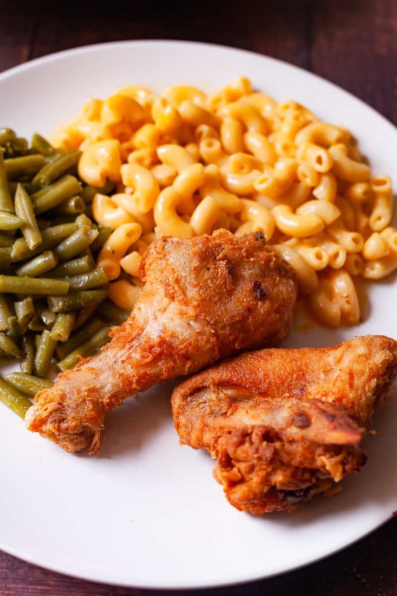 fried chicken on a plate with mac and cheese with green beans