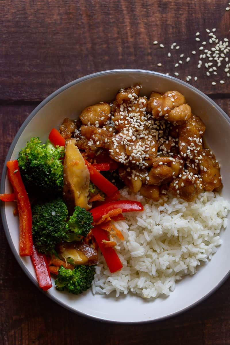 honey ginger chicken in a bowl with rice and vegetables