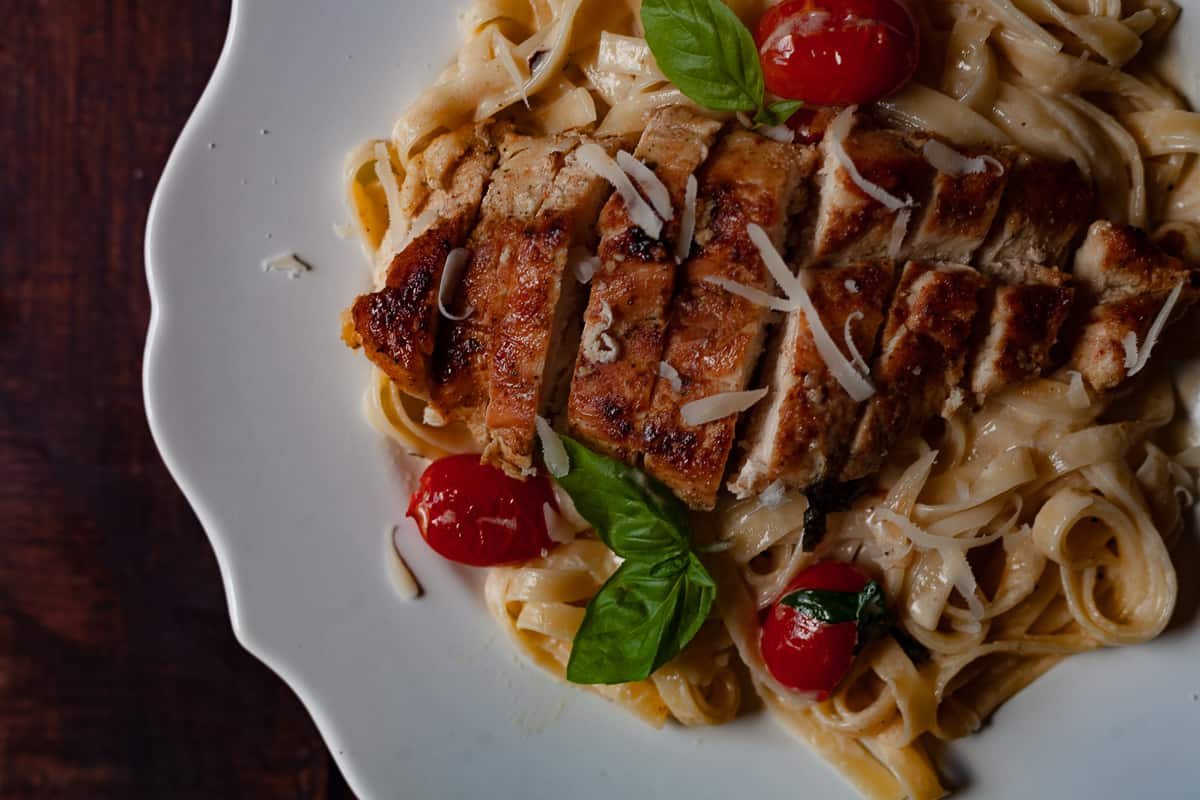plated pan seared chicken over pasta