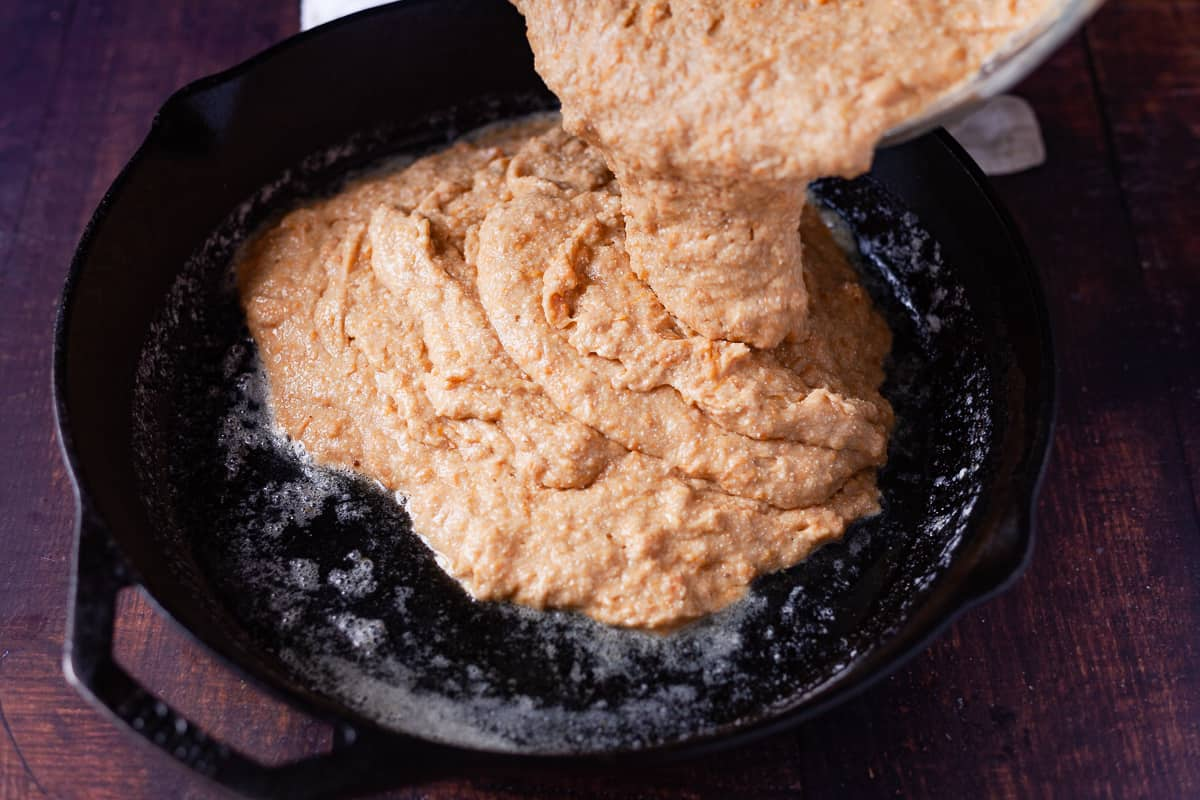 pouring sweet potato cornbread batter into a skillet