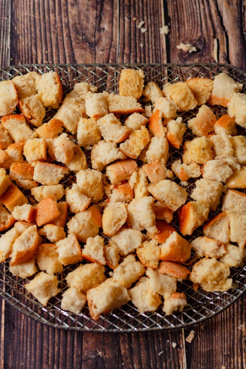 seasoned french bread cubes on an air fryer tray