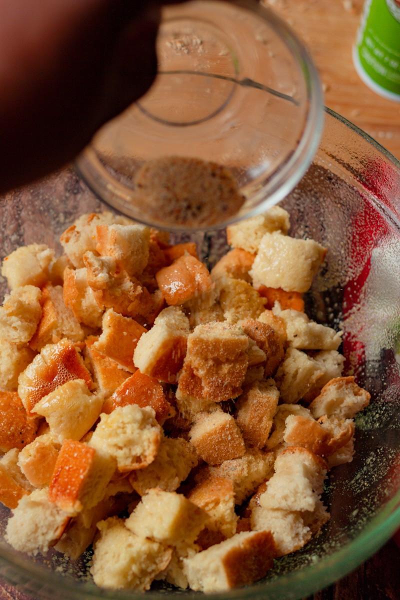 tossing bread cubes in garlic seasoning