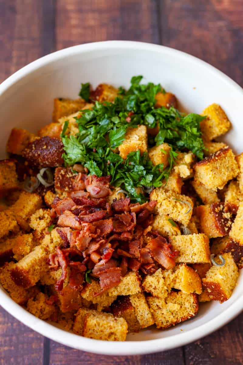 bacon and parsley with cornbread cubes in a large bowl