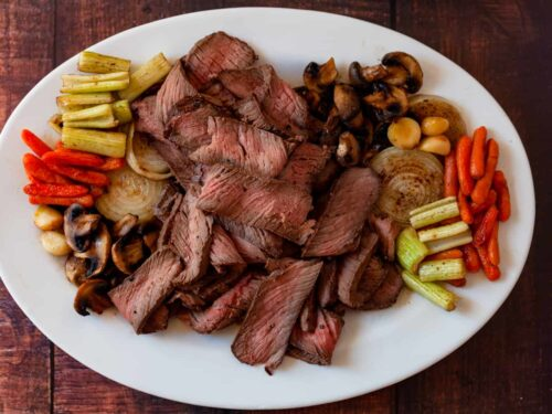 platter of sliced top round roast with roasted vegetables