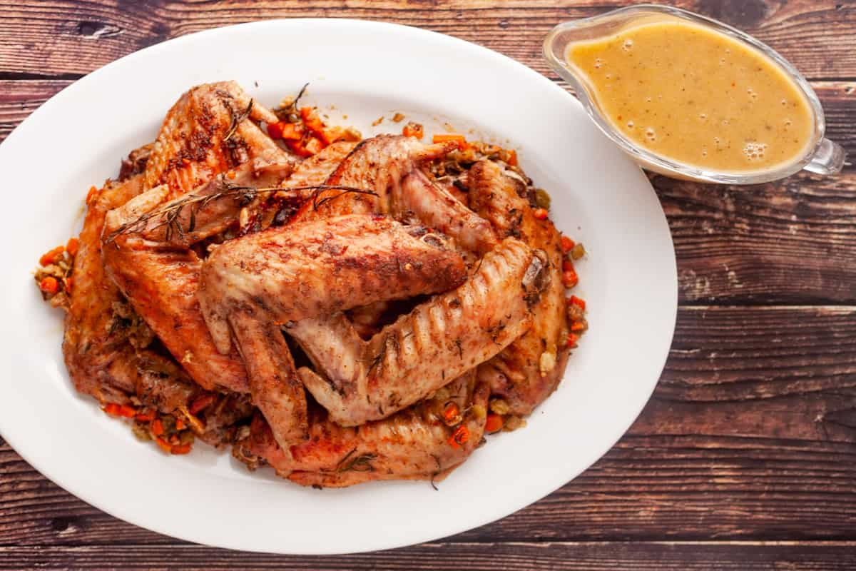 platter of baked turkey wings with and gravy boat
