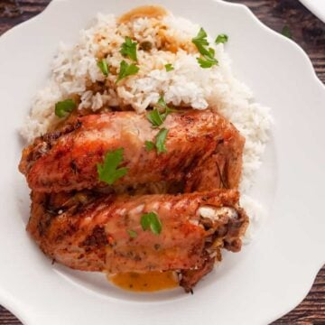 garnished turkey wings on a plate with white rice and gravy