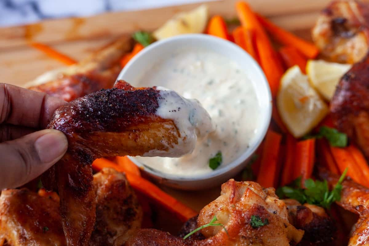 dipping chicken in a bowl of buttermilk dip